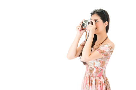 smiling elegant woman wearing summer dress clothing standing on white background and using vintage camera taking picture.