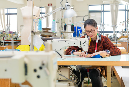 drawing room: beautiful sweet clothing factory sewing woman using tailor machine making new season product in fashion studio with selective focus photo. Stock Photo