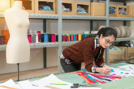 smiling pretty designer woman holding blue zipper looking at sample design draw paper checking whether match and confirm color.