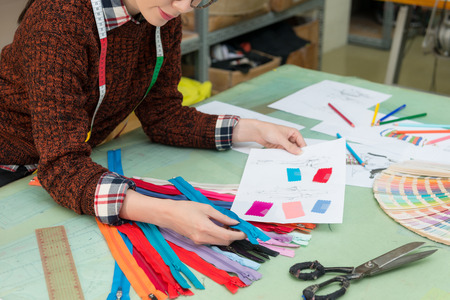 young beautiful clothing manufacturer company female employee using designer drawing file paper choosing right color zipper.