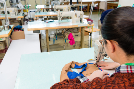 back view photo of professional female clothing designer holding dress sample and using tailor machine sewing designing in fashion factory studio. Фото со стока