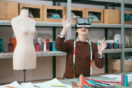 happy attractive clothing factory woman worker wearing virtual reality device looking 3D design video and using hands moving content.