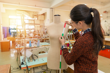 back view angle of pretty clothing making company female employee using tape measuring design product with mannequin dummy in fashion studio. Stock Photo