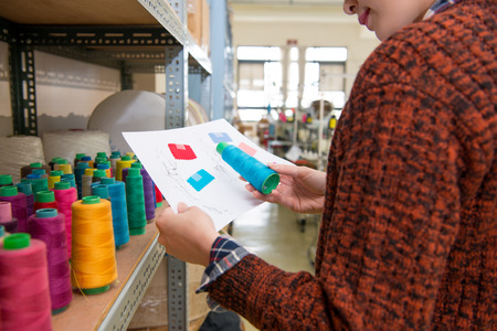 closeup sweet pretty fashion clothing designer holding color design sample paper and choosing blue spool thread checking correct in sewing studio.