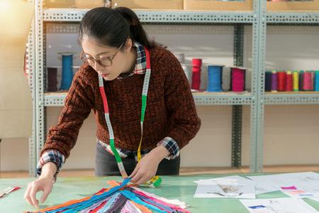 魅力的な美しさの女性の衣料品メーカーは、多くの色のジッパーを整理し、新しいシーズンのための設計製品に zip 一致を選択します。 写真素材