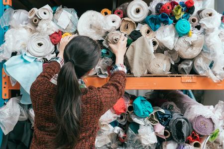 多くの乱雑な生地の前に立って、サンプルを作るために準備ができてデザインの色を選択している若いプロの女性衣料品メーカーのバックビューの 写真素材