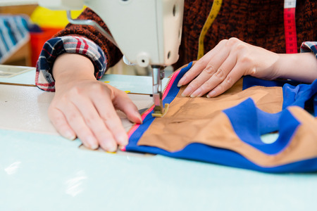 closeup of clothing factory employee woman holding dress sample using tailor machine making for company new season product with selective focus photo.