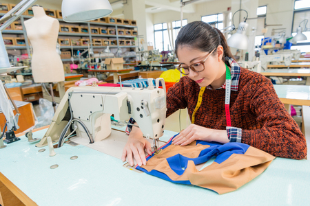 pretty professional female sewing worker using tailor machine making designer new product in fashion studio.