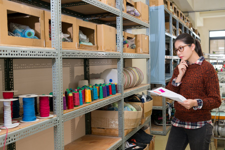 professional young sewing woman holding sample paper looking at color spool threads collection cabinet thinking correct design reel in fashion clothing making studio.