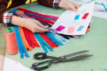 closeup photo of fashion studio female designer choosing zipper confirm design sketch. Zdjęcie Seryjne