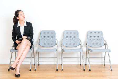 jonge schoonheid kantoormedewerker dame bedrijf persoonlijke voorbereiding document en zittend op houten vloer stoel kijken naar kantoor te wachten voor een interview met een witte achtergrond.