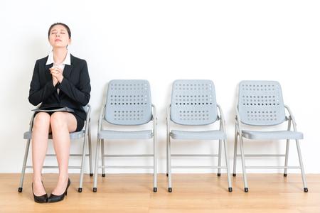 Jeune femme douce diplômée portant un costume en attente d'un nouvel entretien de travail et assise sur une chaise de plancher en bois, faisant un geste de prière, sautant avec succès dans la salle des murs blancs. Banque d'images