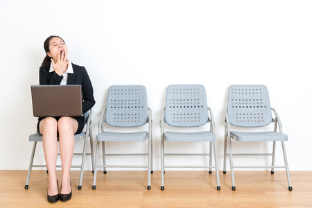 lovely young business female student sitting on wood floor chair waiting for interview meeting feeling tired yawning and holding laptop computer in white wall room. Stock Photo