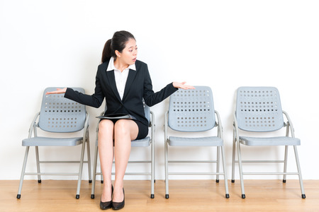 sweet pretty manager female model sitting on wood floor seat chair waiting for work meeting and making choosing gesture feeling confused about only one people join interview at white background.