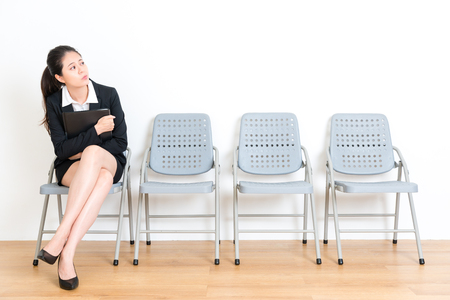 sweet attractive fresh graduate female student sitting on wood floor chair in white wall room and holding personal file waiting for interview.