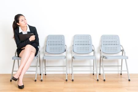 TUdiante diplômée douce douce attrayante, assise sur une chaise de plancher de bois dans la salle de mur blanc et tenant un dossier personnel en attente pour une entrevue Banque d'images - 85941304