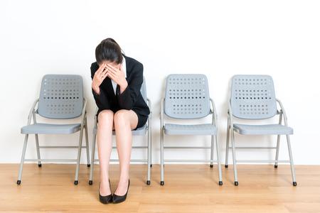 schöne elegante Managerdame, die auf dem Holzfußbodenstuhl stillsteht sitzt, wenn sie das Interviewversagen erhält, das Traurigkeit im weißen Wandhintergrundraum glaubt. Standard-Bild