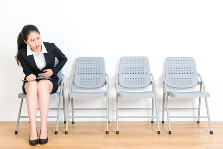ibs: lovely beauty office worker girl waiting for new work interview feeling nervous getting abdomen painful sitting on wood floor chair looking at empty area in white wall background.