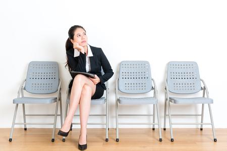 schoonheid mooie zakenvrouw bereiden bedrijfsgegevensbestand zittend op houten vloer stoel in witte muur kamer wachten op interview vergadering verveeld kijken naar lege ruimte fantasie.