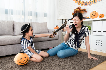 horror girl play the killing game with her mother, using a knife to scared mom put a knife on her head at home