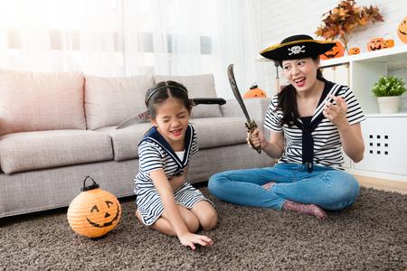 공포 해적 어머니는 그녀의 귀여운 소녀와 살해 게임을하고 거실에있는 할로윈 휴가를 위해 그녀의 머리에 칼을 넣어 스톡 콘텐츠