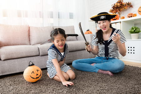 horror pirate mother play the killing game with her cute girl and put the knife on her head for Halloween holiday in the living room