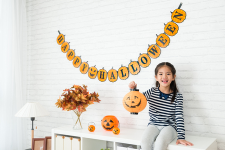 happy kids holding a pumpkin lantern and sitting on the cabinet of the living room after help her family to decorating 스톡 콘텐츠