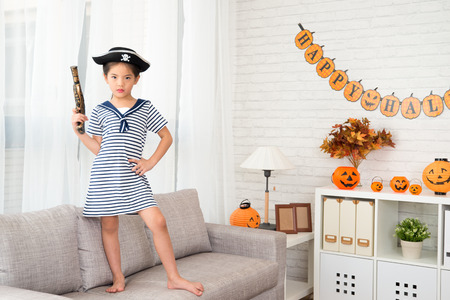 serious confidence naughty captain girl holding a pirate toy pistol have fun for Halloween holiday standing on sofa at home