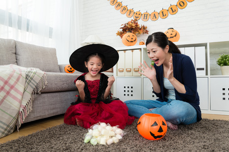 happy girl feel success and her shocked mother to see many candies from Trick or treat the game of Halloween Imagens