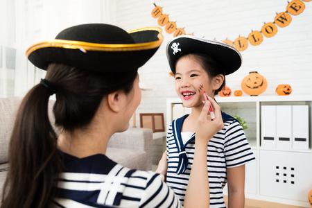 piraat meisje en moeder spelen Halloween make-up spel en schets littekens op het gezicht thuis Stockfoto