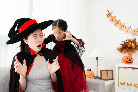 naughty little witch girl scared her mother from the back have fun in the living room at home Stock Photo