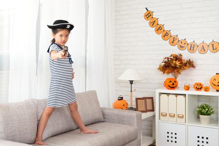 ondeugende kapitein meisje met een piraat speelgoed pistool doel naar de camera thuis