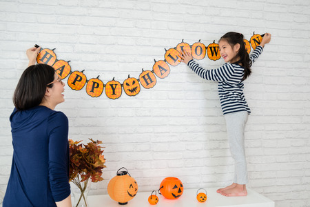 Happy family prepares for Halloween, Young mom and her kids hanging up the decoration celebrate the holidays.