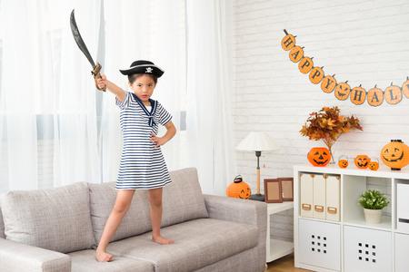 小さな海賊の女の子がパーティーでゲーム ハロウィーンのために戦う決意を示すナイフ所持