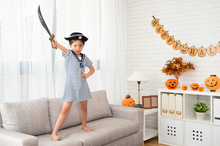 little pirate girl holding knife showing her determination to fight for Halloween game at the party Stock Photo