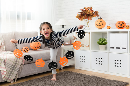 happy kid feel excited to showing the halloween paper decorations before the party in the living room at home Stock Photo