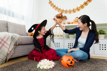 beauty girl and her mother celebrate she obtain many sweet candies from Halloween play game