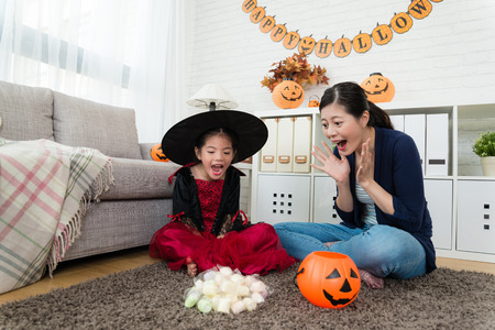 sweet girl and her mother shocked to see many candies from Trick or treat the game of Halloween Imagens - 86108081