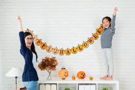 Happy family prepares for Halloween together, Young mom and her kids hanging up the decoration stick on the wall, celebrate the holidays at home.