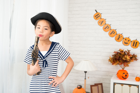 little pirate girl blowing toy gun after shooting have fun with her friends at Halloween party at home