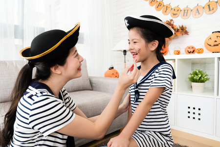 pirate girl and mother have fun with Halloween makeup drawing scars on the face at home