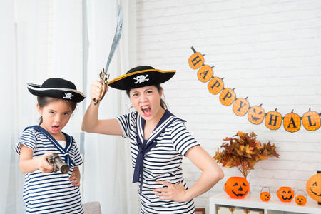 crazy captain girl and crew mother play the pirate game for Halloween holiday at home