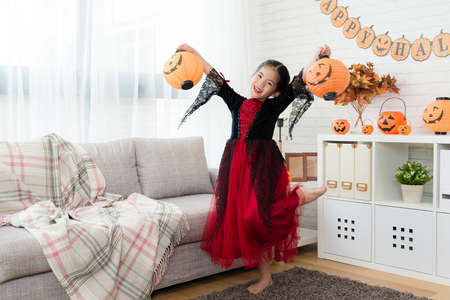 sweet happy girl wear Halloween costume dress and holding two pumpkin lantern to dance at home Stock Photo