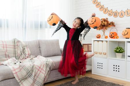 zoet blij meisje draag Halloween kostuum jurk en houdt twee pompoen lantaarn om thuis te dansen Stockfoto