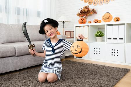 schattig meisje draag het piraatkostuum en houdt een pompoenlantaarn spel in Halloween en zit op de vloer in de woonkamer