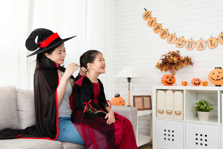 beautiful mother wearing vampire cloak to helping her happy daughter to dress up for Halloween party