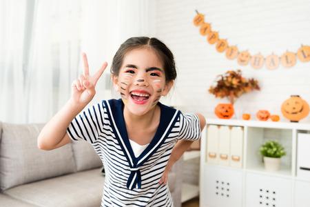 schattig klein meisje speelt make-up gereedschap van haar moeder en zet rotzooi puttend uit haar gezicht voor Halloween-voorbereiding
