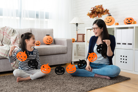 school kid holding the Halloween paper cut decorations with her mother and look at each other sitting in the living room Фото со стока