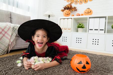 Halloween game trick or treat에 대 한 호박 컨테이너에서 그녀의 달콤한 사탕을 들고 귀여운 행복 소녀. 스톡 콘텐츠