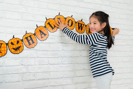 lieve kinderen helpen haar familie om de decoratie op te hangen om de Halloween-vakantie thuis te vieren.
